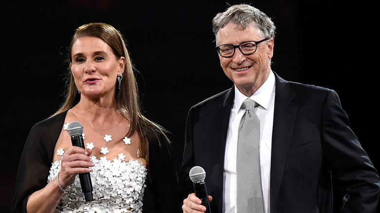 Melinda e Bill Gates parlano e sorridono tenendo in mano i microfoni