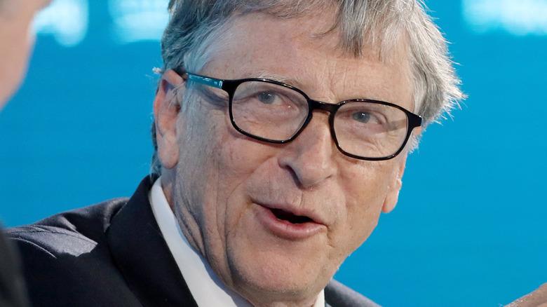 Bill Gates parla e guarda alla sua destra con un paio di occhiali