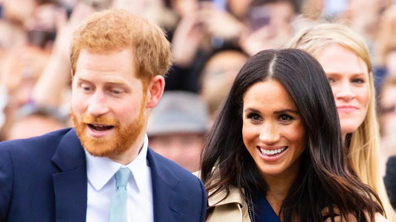 Il principe Harry e Meghan Markle sorridono a un evento pubblico in Australia
