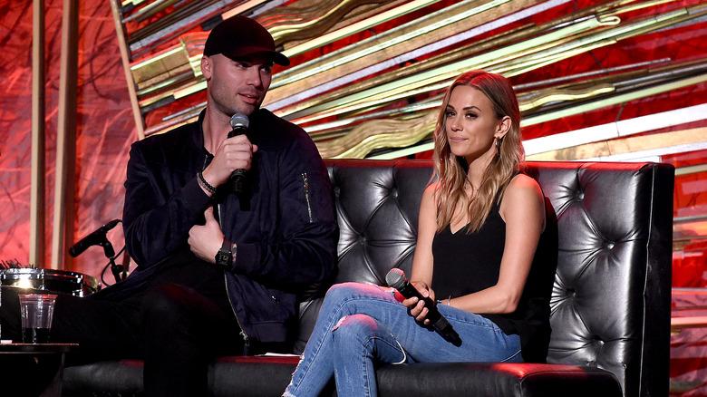 Mike Caussin, che indossa abiti scuri e un cappello, parla in un microfono;  Jana Kramer, seduta su un divano, sembra infastidita, indossa jeans, foto del 2019