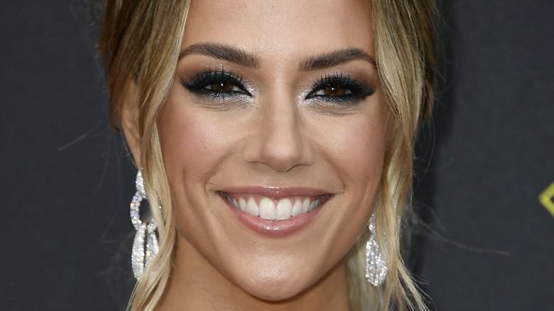 Jana Kramer, sorridente, truccata, orecchini grandi, capelli raccolti, foto del 2019