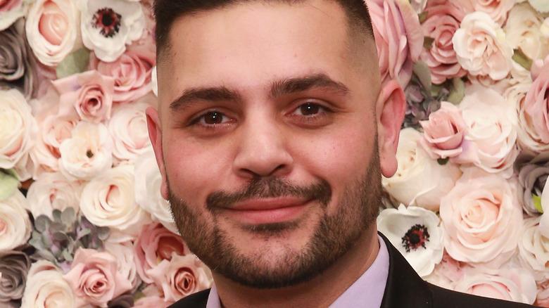 Michael Costello davanti a un muro di fiori