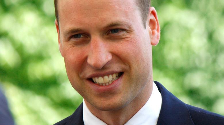 Il principe William sorride e guarda dalla parte