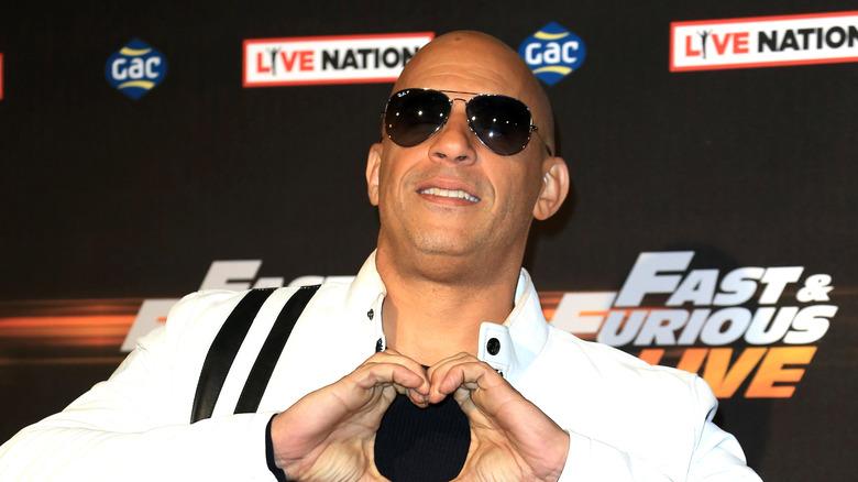 Vin Diesel indossa occhiali da sole e fa un cuore con le mani