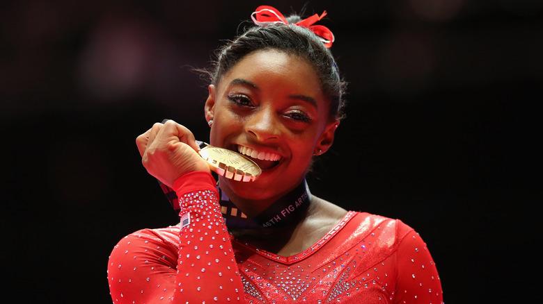 Simone Biles che morde la medaglia