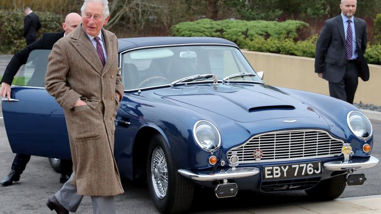 Il principe Carlo cammina accanto alla sua Aston Martin